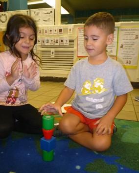 Niña y niño jugando con figuras geométricas