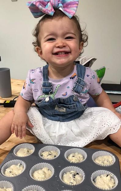 Bebé sonríe sentada frente a algunos productos para hornear