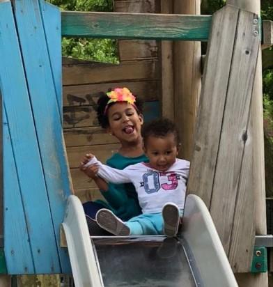 Hermana y hermano juegan en el pation