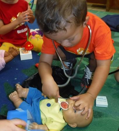 Niño jugando al médico con un muñeco