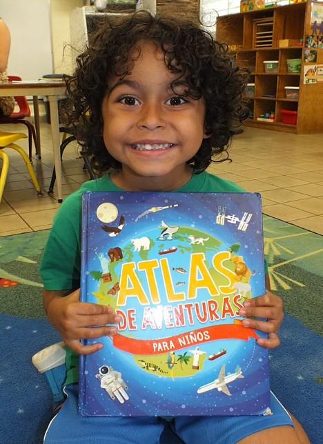 Niño muestra su libro de aventuras