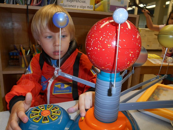 Niño juega con un modelo del sistema solar para principiantes